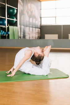 Criança de menina pequena flexível exercício no tapete verde no ginásio