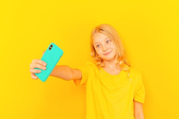 Criança de menina sorridente mostrando a tela azul do novo telefone móvel popular sobre fundo amarelo claro.