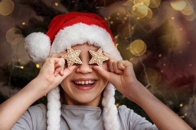 Criança de natal com chapéu de papai noel segurando um pão de mel em forma de estrelas na frente dos olhos
