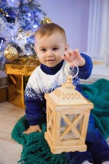 Criança de natal, menino feliz brincando, criança sentada na frente da árvore de natal.