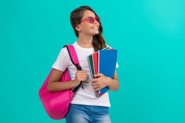 Criança de óculos segura o caderno. 1 de setembro. infância. filho de estudante com mochila escolar pronta para estudar. menina adolescente feliz carrega a mochila e o caderno. de volta à escola. dia do conhecimento. educação.