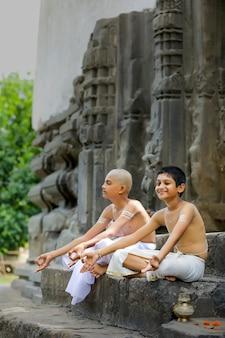 Criança de padre indiano fazendo ioga no parque