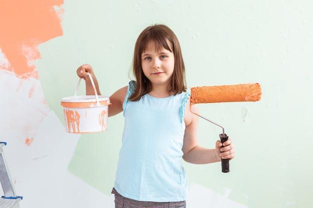 Criança de pé com rolo de pintura na mão. ela está pintando a parede. redecorar, reparar e repintar
