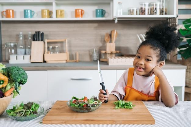 Criança de pele negra com salada no prato na cozinha