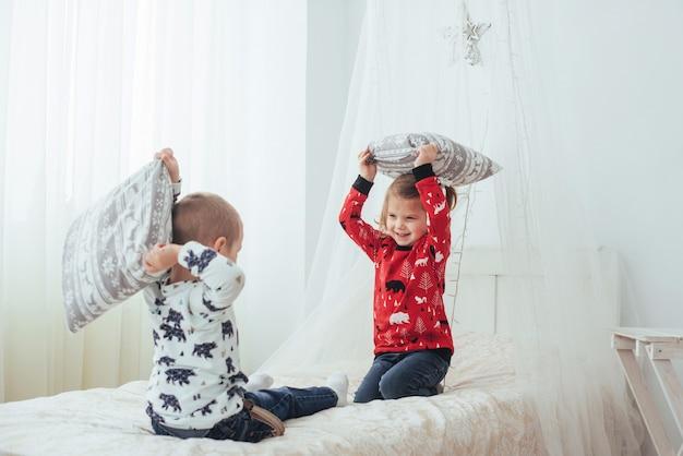Criança de pijama macio e quente brincando na cama