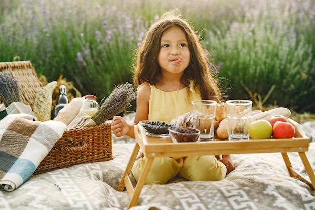 Criança de provença relaxante no campo de lavanda. menina em um piquenique.