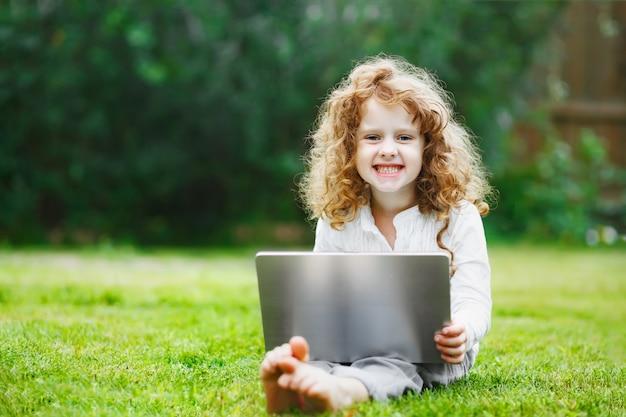 Criança de riso que trabalha com o caderno que mostra os dentes brancos saudáveis.