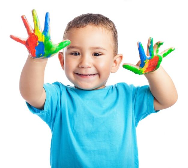 Criança de sorriso com as mãos cheias de tinta