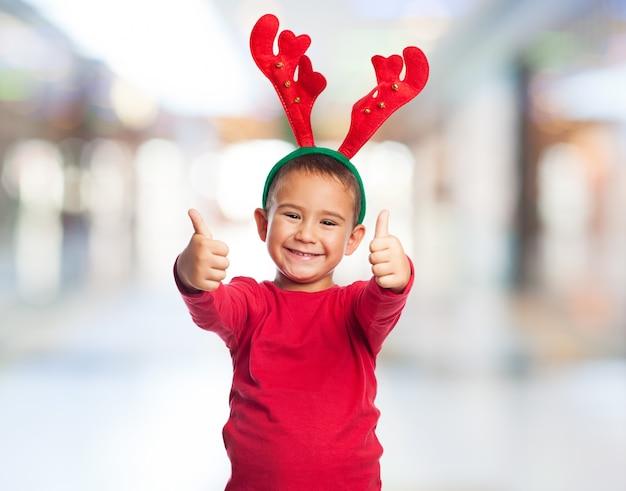 Criança de sorriso que mostra uma cabeça com chifres