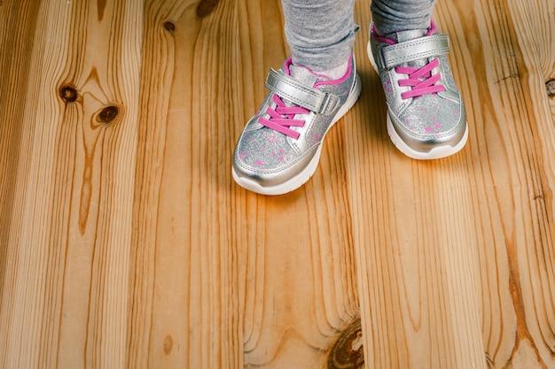 Criança de tênis na superfície de madeira