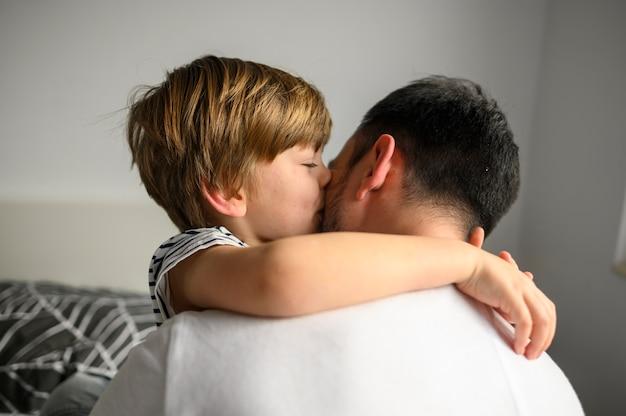 Criança de tiro médio, abraçando seu pai