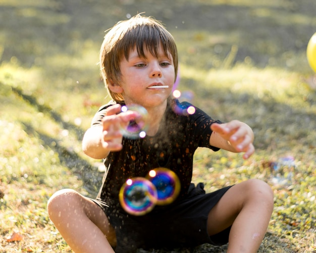 Criança de tiro médio brincando com bolhas de sabão