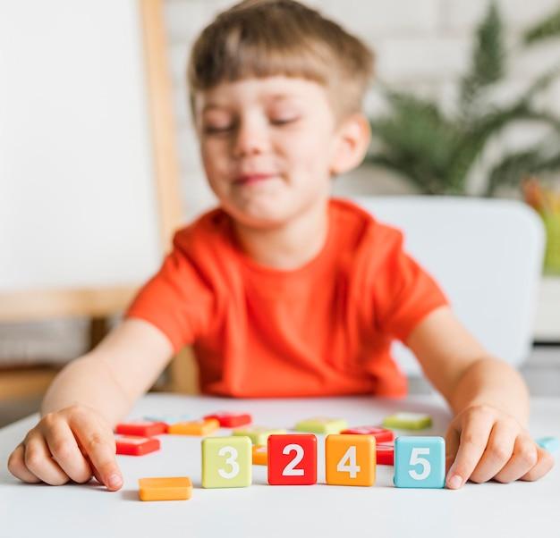 Criança de tiro médio brincando com números