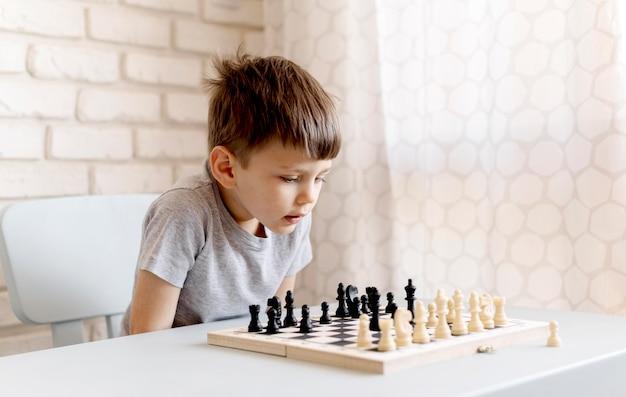 Criança de tiro médio com jogo de xadrez