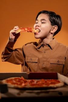 Criança de tiro médio comendo pizza