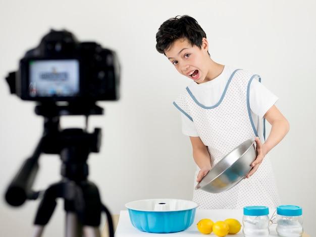 Criança de tiro médio cozinhando na câmera