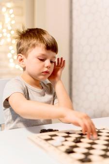 Criança de tiro médio jogando xadrez