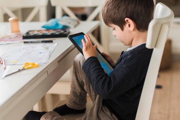 Criança de tiro médio na cadeira com tablet