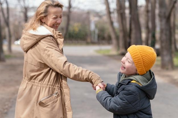 Criança de tiro médio segurando a mão de uma mulher