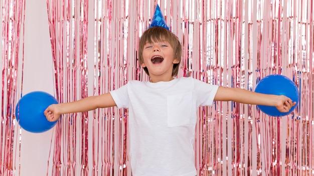 Criança de tiro médio segurando balões azuis