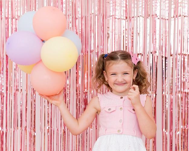 Criança de tiro médio segurando balões