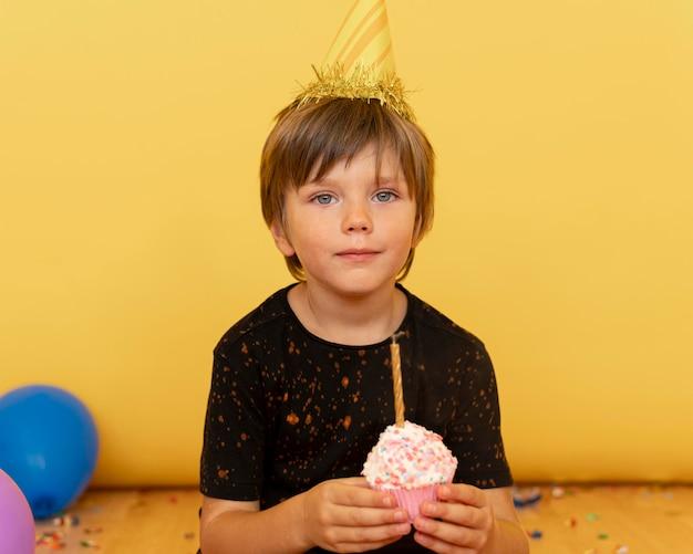 Criança de tiro médio segurando cupcake com vela