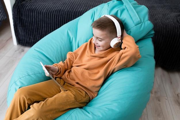 Criança de tiro médio segurando fones de ouvido