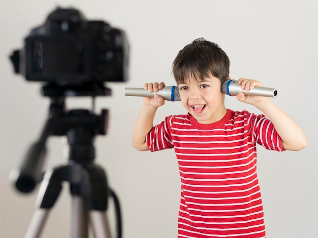 Criança de tiro médio segurando microfones