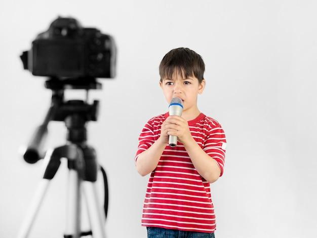 Criança de tiro médio segurando o microfone