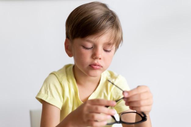 Criança de tiro médio segurando óculos