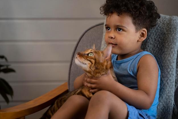 Criança de tiro médio segurando um gato fofo