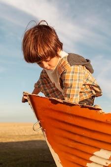 Criança de tiro médio sentado em um barco
