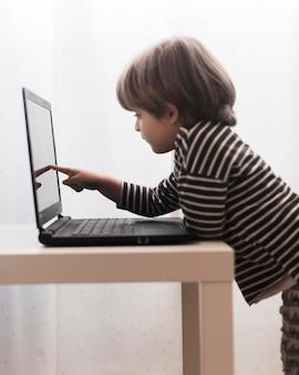 Criança de tiro médio tocando laptop
