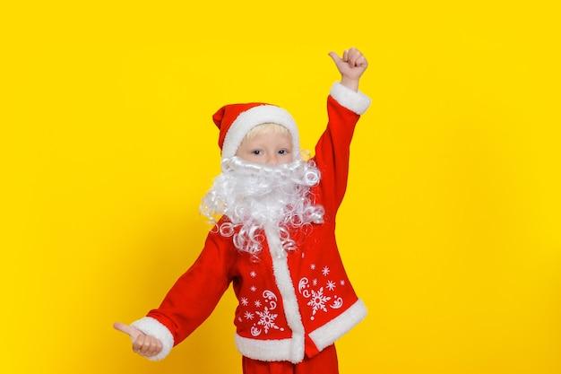 Criança de três anos com roupa de papai noel e barba branca mostra um gesto de polegar para cima