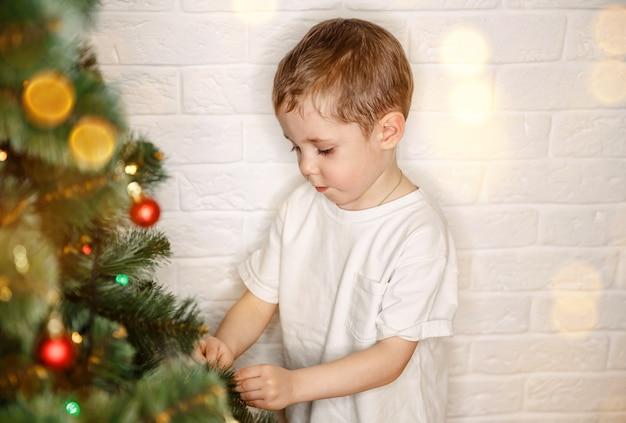 Criança decora árvore de natal em casa criança na véspera de natal
