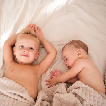 Criança deitada ao lado de bebê