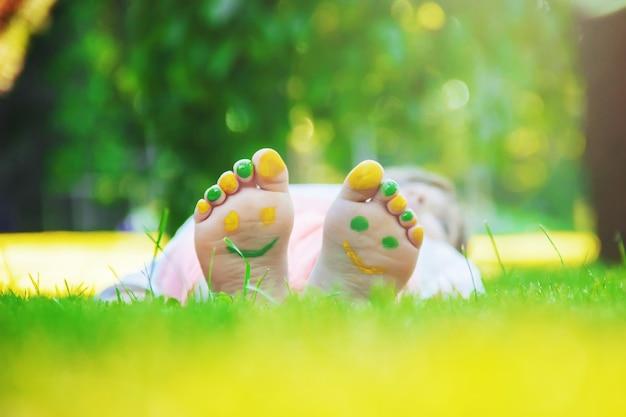 Criança deitada na grama verde. garoto se divertindo ao ar livre no parque primavera.