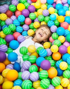 Criança deitada na piscina com bolas de plástico