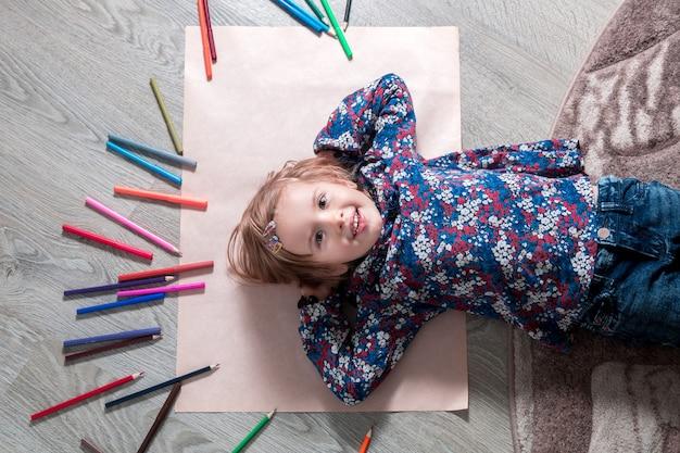Criança deitada no chão em papel, olhando para a câmera perto de giz de cera. pintura, desenho.