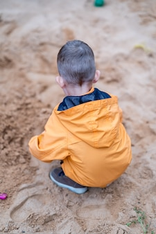 Criança deixada sozinha sem supervisão na caixa de areia do playground Foto Premium