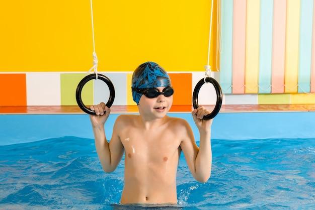 Criança dentro da piscina excersizing com argolas esportivas