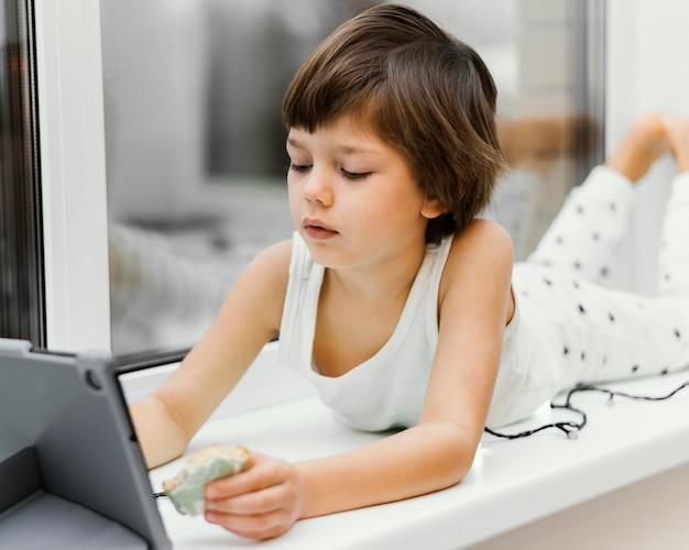 Criança dentro de casa olhando para o tablet