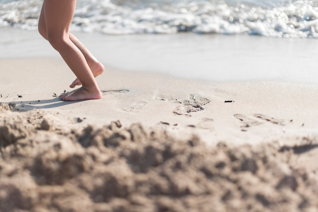 Criança descalça brincando à beira-mar