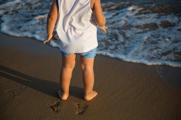 Criança descalça pelo mar