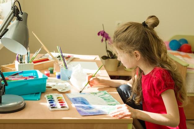 Criança desenha aquarela na mesa em casa