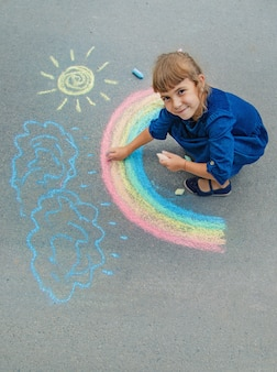 Criança desenha com giz na calçada