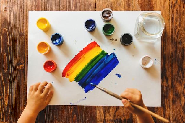 Criança desenha com guache pintar um arco-íris