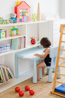 Criança desenha com lápis, sentado à mesa no quarto das crianças.