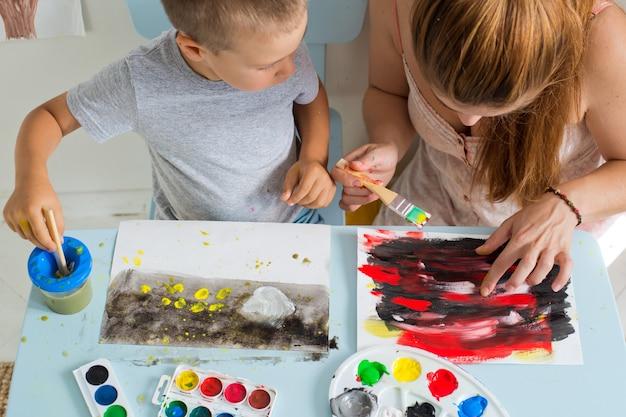 Criança desenha com o professor