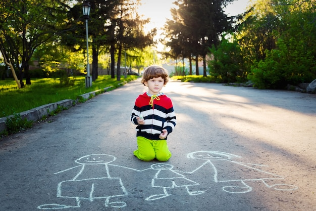 Criança desenha no asfalto.